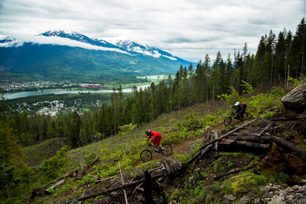 Riders on a downhill trail overlooking Revelstoke